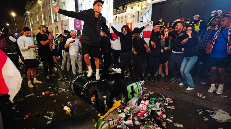 English fans kick and stand on a litter bin in Piccadilly Circus following the match