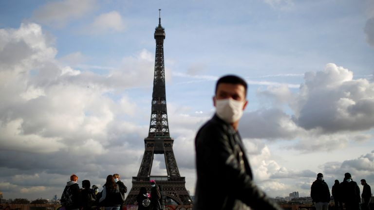 FILE PHOTO: A man, wearing protective face mask, walks at Trocadero square near the Eiffel Tower in Paris amid the coronavirus disease (COVID-19) outbreak in France, January 22, 2021. REUTERS/Gonzalo Fuentes/File Photo