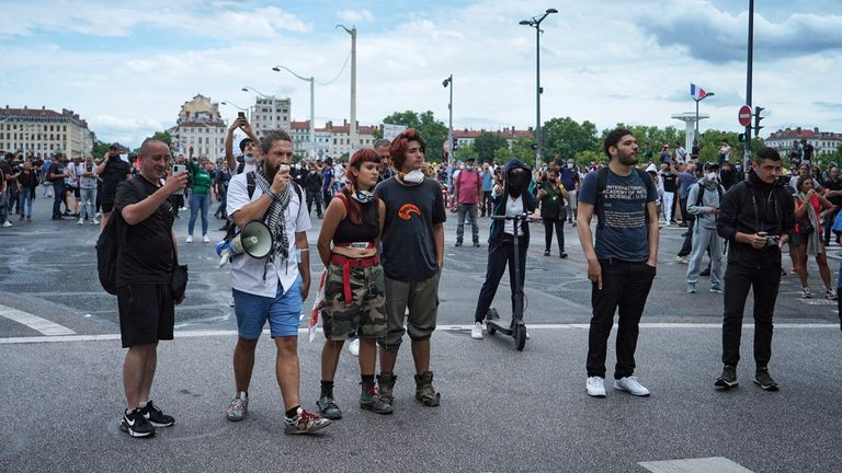 Protestors stand in front of policemen during a demonstration in Lyon, central France, Saturday, July 31, 2021. Demonstrators gathered in several cities in France on Saturday to protest against the COVID-19 pass, which grants vaccinated individuals greater ease of access to venues. (AP Photo/Laurent Cipriani)