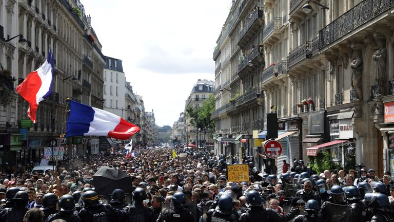 Protestors march waving French flags during a demonstration in Paris, France, Saturday, July 31, 2021. Demonstrators gathered in several cities in France on Saturday to protest against the COVID-19 pass, which grants vaccinated individuals greater ease of access to venues. (AP Photo/Adrienne Surprenant)