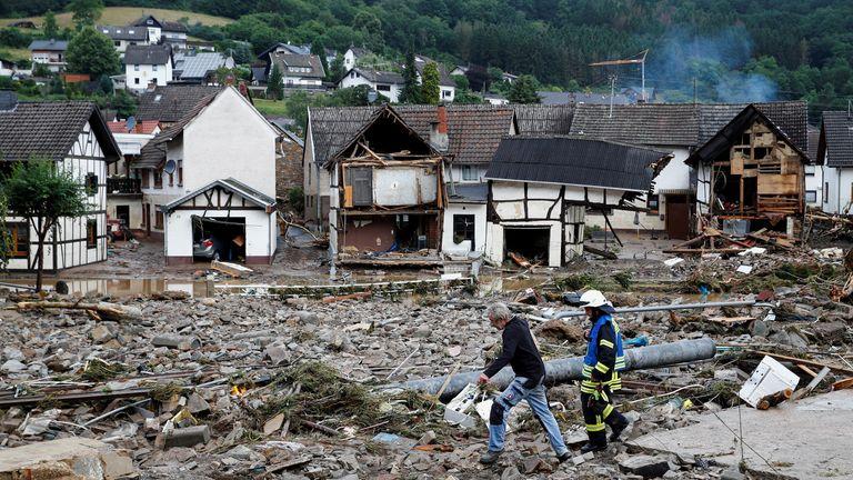 A man and firefighter walk through debris, following heavy rainfalls in Schuld, Germany