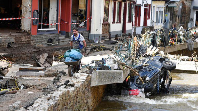A man carries debris along Erft river in Bad Munstereifel. Pic: AP