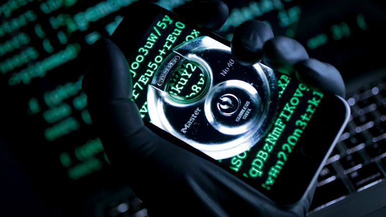 Hand grabs an iPhone displaying a strong padlock and the sample public key of encryption software. Pic: AP