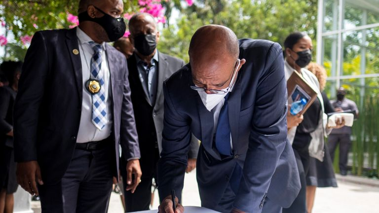 Ariel Henry signs a condolence for late Haitian President Jovenel Moise