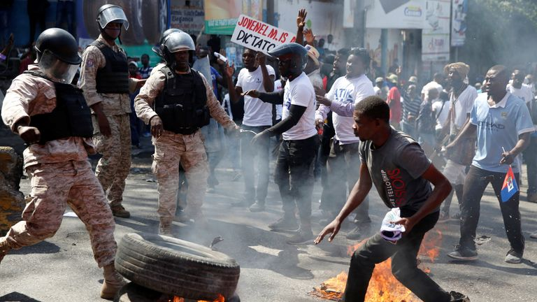 Barricades burn in Haiti in protest against President Jovenel Moise Police officers look on as demonstrators take part in a march during a protest against Haiti's President Jovenel Moise, in Port-au-Prince, Haiti February 14, 2021. REUTERS/Jeanty Junior Augustin