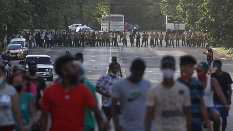 Demonstrators walk away from army soldiers blocking a road in Havana