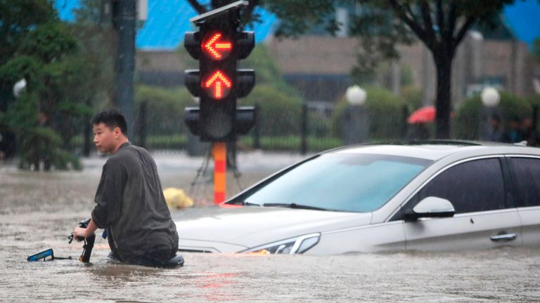 A man rides a bicycle through a flooded intersection in Zhengzhou in central Chinas Henan Province (Chinatopix via AP)