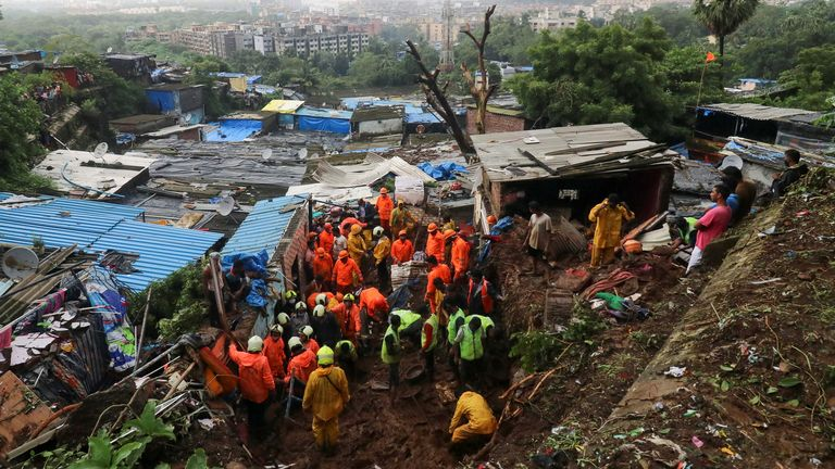Rescue workers remove debris as they search for survivors after a residential house collapsed due to landslides caused by heavy rainfall in Mumbai