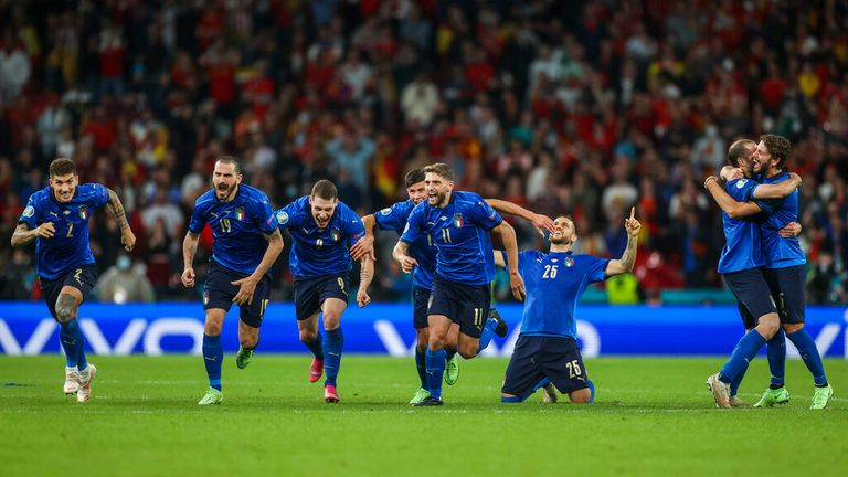 The Italians rush towards Jorginho after he sealed their place in the final. Pic: AP