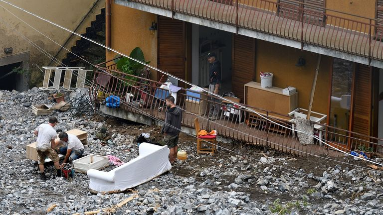 People work after a landslide hit a house after heavy rain caused flooding