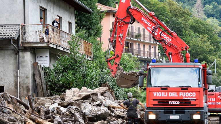 Firefighters remove debris from a landslide after the extreme weather