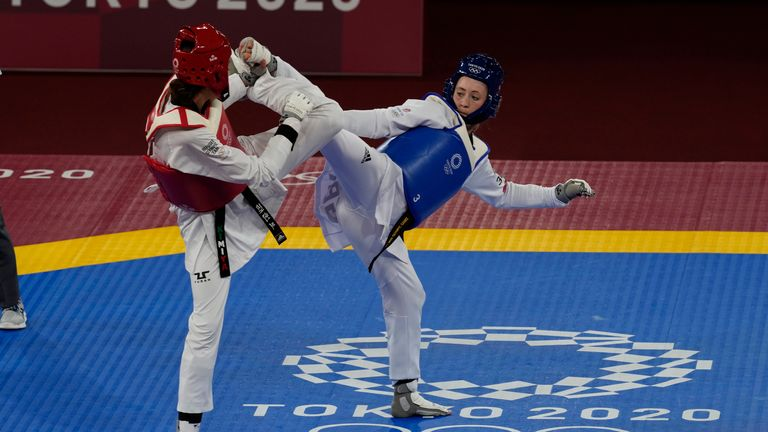 Britain's Jade Jones, right, challenges Kimia Alizadeh Zonoozi, Refugee Olympic Team, during the taekwondo women's 57kg match at the 2020 Summer Olympics, Sunday, July 25, 2021, in Tokyo, Japan. (AP Photo/Themba Hadebe)