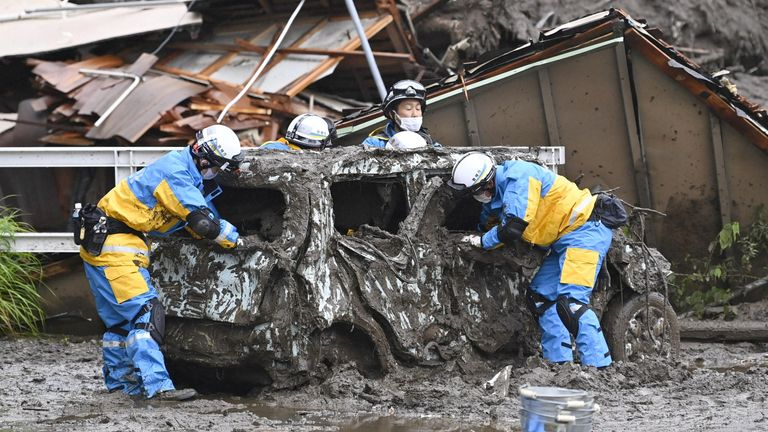 Police officers conduct search and rescue operation around a destroyed car at a mudslide site caused by heavy rain at Izusan district in Atami