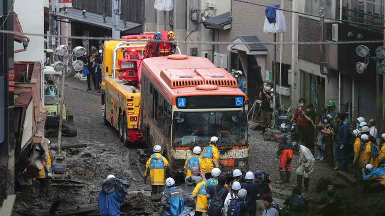 A wrecked bus is removed from debris flow site in Atami City, Shizuoka Prefecture on July 5, 2021. A large-scale mudslide triggered by torrential rain occurred in Atami on July 3rd, as a seasonal front brought heavy downpours to areas across the Kanto and Tokai regions. It is estimated that there are many dead and missing person.   ( The Yomiuri Shimbun via AP Images )