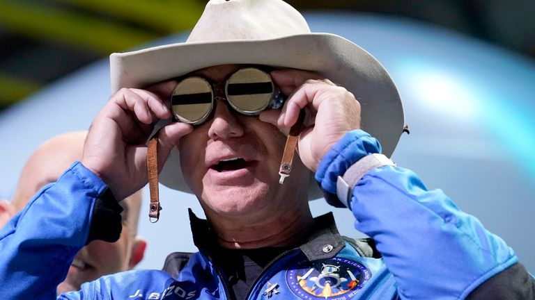 Jeff Bezos puts goggles over his eyes that belonged to aviator Amelia Mary Earhart during a post-launch news briefing. Pic: AP