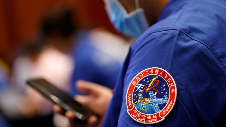 A badge of the Shenzhou-12 Manned Space Flight Mission is seen on the uniform of a staff member of the Jiuquan Satellite Launch Center during a news conference before the Shenzhou-12 mission to build China's space station, at Jiuquan Satellite Launch Center in Gansu province, China June 16, 2021. REUTERS/Carlos Garcia Rawlins