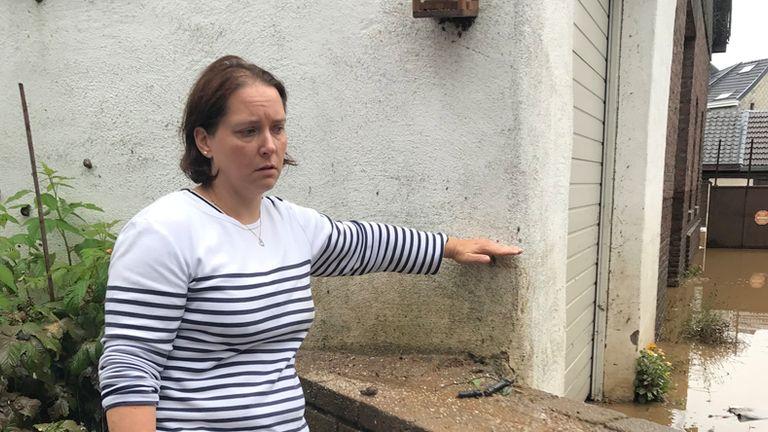Laetita Colin usa la mano per mostrare quanto è alta l'acqua in casa sua