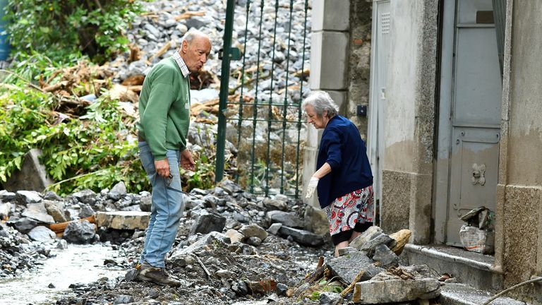 People clean debris in front of their house after heavy rain caused flooding