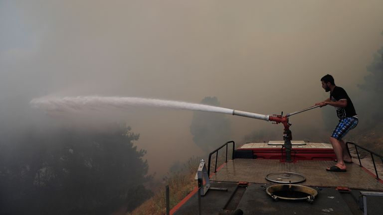 A man sprays water canon to extinguish forest fire, at Qobayat village, in the northern Akkar province, Lebanon, Thursday, July 29, 2021. Lebanese firefighters are struggling for the second day to contain wildfires in the country's north that have spread across the border into Syria, civil defense officials in both countries said Thursday. (AP Photo/Hussein Malla)