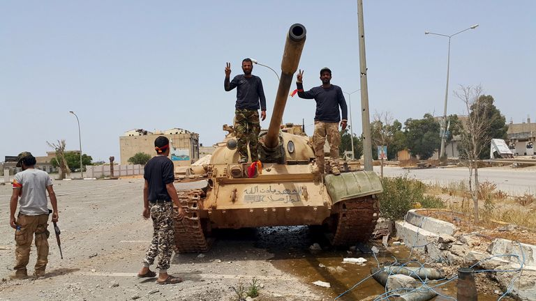 Members of the Libyan pro-government forces gesture as they stand on a tank in Benghazi, Libya, 21 May, 2015