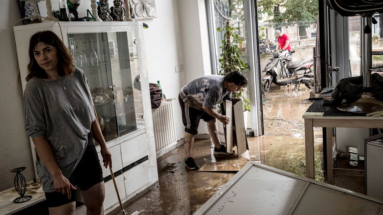 People clean their home in Liege, Belgium. Pic: Associated Press