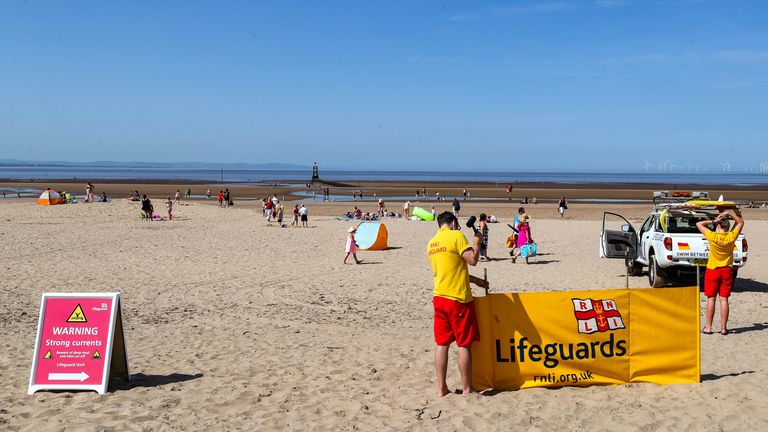 Three men were taken to hospital after they came into difficulties at Crosby Beach near Liverpool