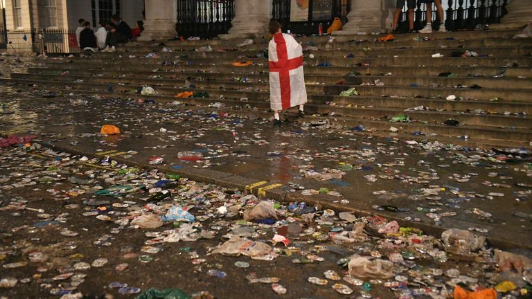 An England fan draped in a flag walks amongst the litter strewn on the ground in front of St Martin-In-The-Fields church, in Trafalgar Square, London, after Italy beat England on penalties to win the UEFA Euro 2020 Final. Picture date: Sunday July 11, 2021.