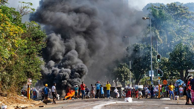 Looters outside a shopping centre alongside a burning barricade in Durban. Pic: AP