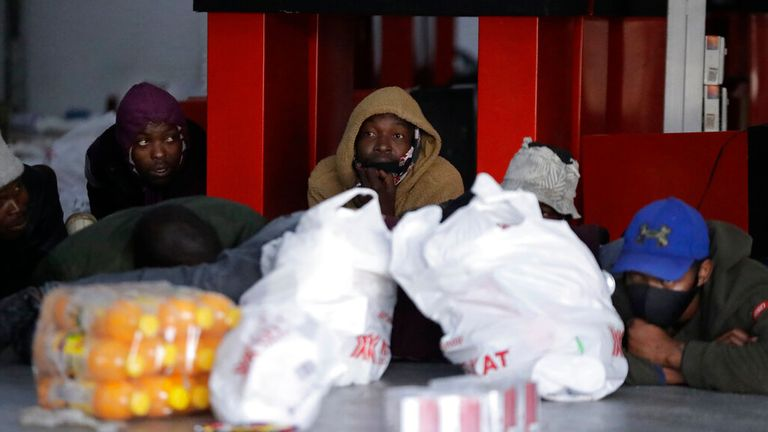 Apprehended looters with their goods on the floor inside a store in Vosloorus near Johannesburg