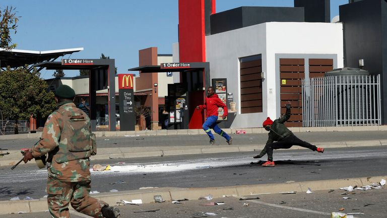 A soldier apprehends looters at a shopping centre as violence escalates