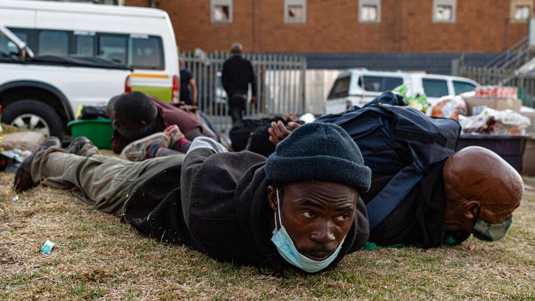 Suspect looters are held at a taxi rank shops in Soweto, Johannesburg