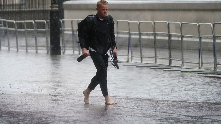 One gentleman thought it would be a good idea to take his shoes off as larges puddles formed in central London