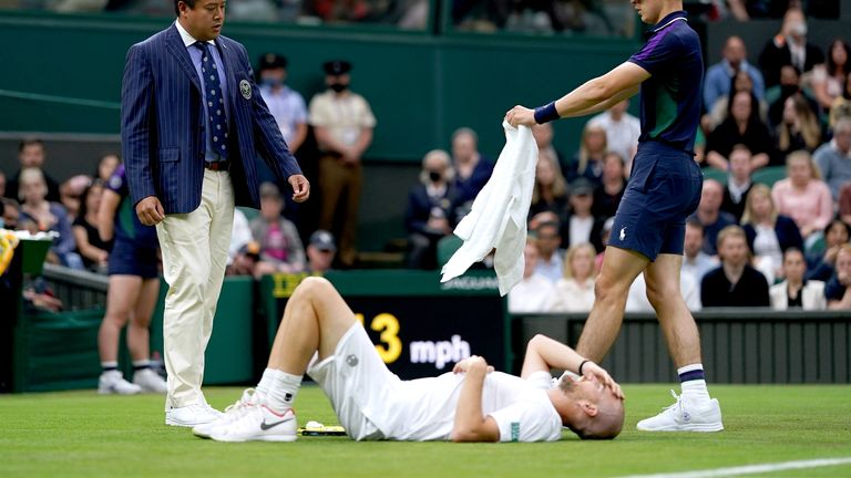Adrian Mannarino slips on the grass and injures his leg during his first round gentlemen's singles match against Roger Federer on centre court on day two of Wimbledon at The All England Lawn Tennis and Croquet Club, Wimbledon. Picture date: Tuesday June 29, 2021.