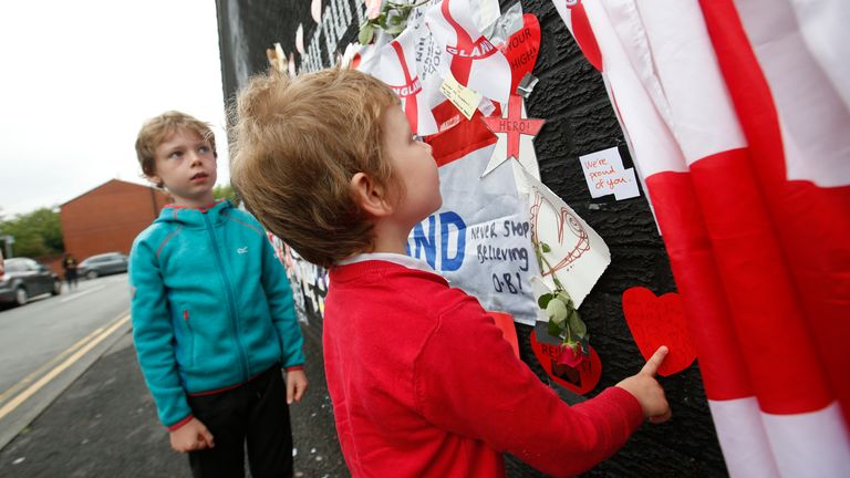 Children look at some of the messages on the Marcus Rashford mural