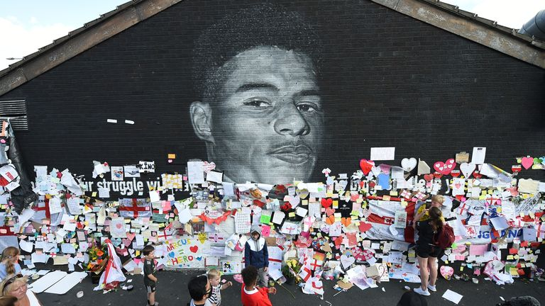 Soccer Football - Stand Up to Racism Demonstration at the Marcus Rashford mural after it was defaced following the Euro 2020 Final between Italy and England - Withington, Manchester, Britain - July 13, 2021 People look at messages of support on the Marcus Rashford mural after it was defaced following the Euro 2020 Final between Italy and England REUTERS/Peter Powell