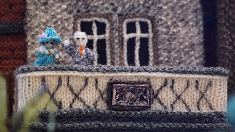 The piece includes miniature woollen versions of the Queen and the Duke of Edinburgh on a balcony