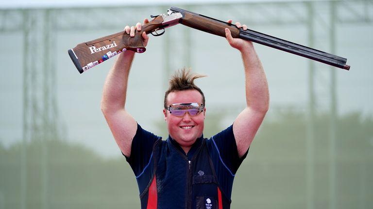 Matthew Coward-Holley raises his gun after winning a bronze medal