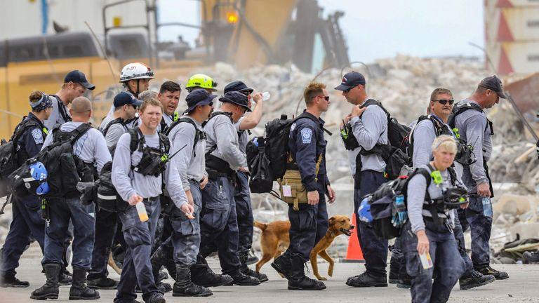 Anggota tim SAR berangkat setelah bekerja di ladang puing di kondominium tepi laut 12 lantai, Champlain Towers South di Surfside pada Rabu, 7 Juli 2021.