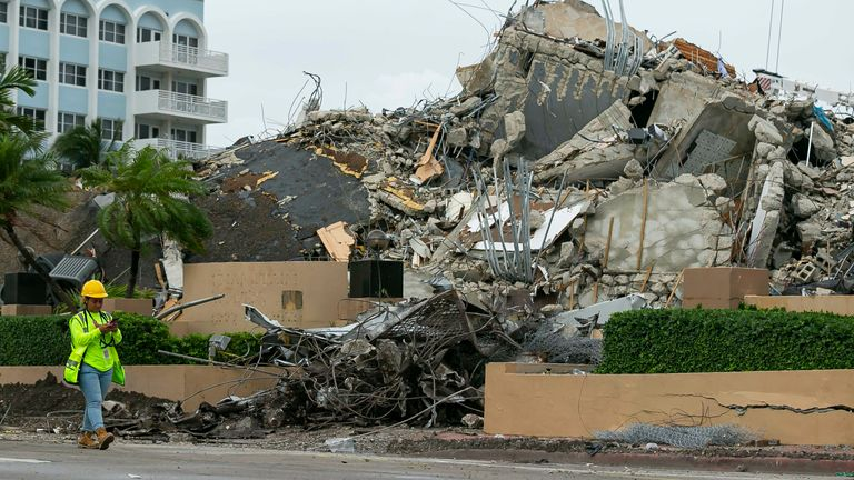 A workers make her way past the rubble and debris of the Champlain Towers South condo in Surfside, Florida on Tuesday, July 6, 2021. The rubble shown here is from the front portion of the condo towers, which was demolished 11 days after the back part of the tower collapsed with people inside.