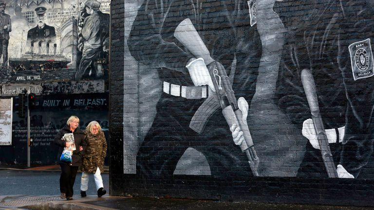Women walk past a Loyalist Paramilitary mural on the Newtonard's Road area of East Belfast November 20, 2013