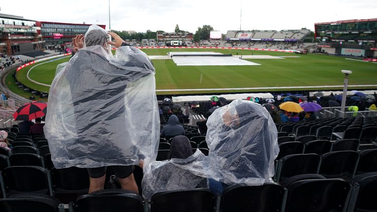 Spectators shelter umbrellas during a pitch inspection ahead of The Hundred match at the Emirates Old Trafford, Manchester