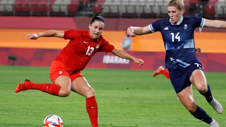 Jul 27, 2021; Ibaraki, Japan; Canada player Evelyne Viens (13) kicks the ball while being defended by Great Britain player Millie Bright (14) during the Tokyo 2020 Olympic Summer Games at Ibaraki Kashima Stadium. Mandatory Credit: Geoff Burke-USA TODAY Sports