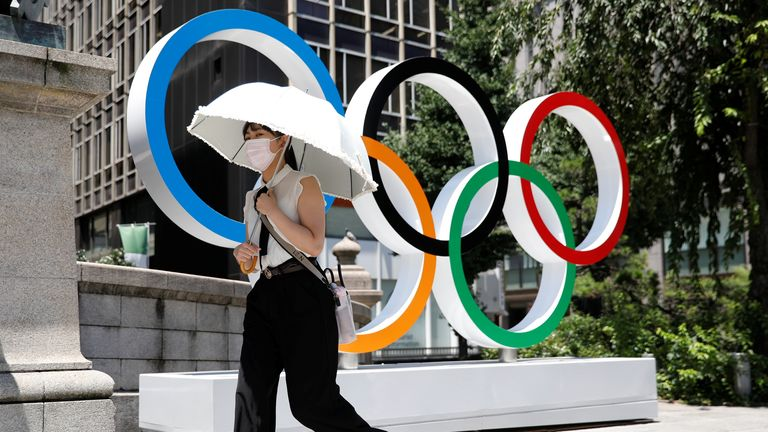 A woman walks past the Olympics rings in Tokyo