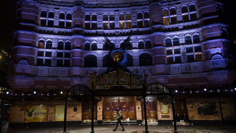 A man walks past the Palace Theatre in London, which is closed as the area has moved into the highest tier of coronavirus restrictions as a result of soaring case rates.