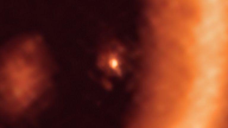Cette image, prise avec l'Atacama Large Millimeter/submillimeter Array (ALMA), dont l'ESO est partenaire, montre une vue rapprochée du disque lunaire entourant PDS 70c, une jeune géante gazeuse semblable à Jupiter de près de 400 lumières. ans de distance.  Il montre cette planète et son disque au centre de l'avant, le plus grand disque en forme d'anneau circumstellaire occupant la majeure partie du côté droit de l'image.  Le disque poussiéreux... circumplanétaire est aussi grand que la distance Soleil-Terre et a une masse suffisante pour former jusqu'à trois satellites de la taille de la Lune.