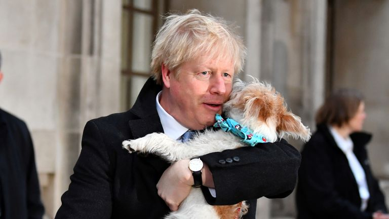 FILE PHOTO: Britain's Prime Minister Boris Johnson holds his dog Dilyn as he leaves a polling station, at the Methodist Central Hall, after voting in the general election in London, Britain, December 12, 2019. REUTERS/Dylan Martinez/File Photo