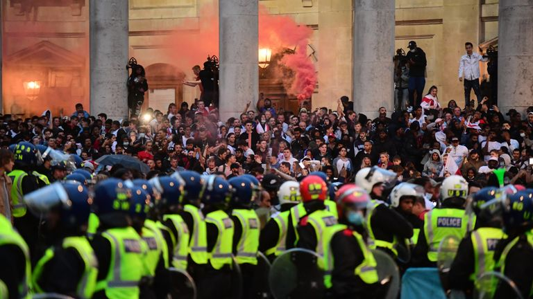 olice officers observe England fans letting off flares on the steps of the St Martin-In-The-Fields church, in Trafalgar Square, London during the UEFA Euro 2020 Final between Italy and England. Picture date: Sunday July 11, 2021.