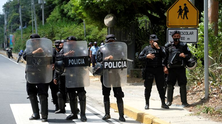 Nicaraguan police officers stand in formation as they block journalists working outside the house of opposition leader Cristiana Chamorro
