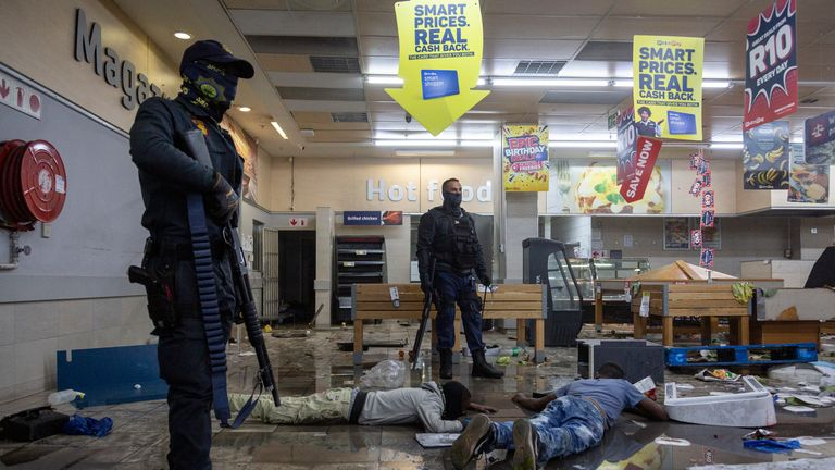 Police stand over detained suspected looters in a shopping centre in Alexandra township, Johannesburg