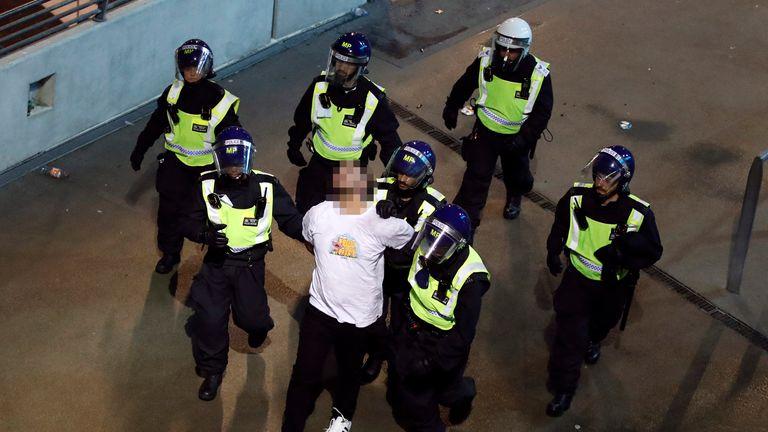 Police detain a fan outside Wembley